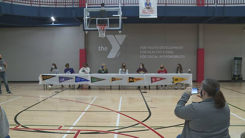 Eight swimmers from the Woodson YMCA Northern Swimmers team celebrate signing their letters of...