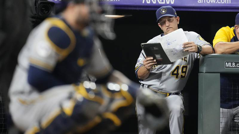 Milwaukee Brewers hitting coach Andy Haines studies notes while the Colorado Rockies bat during...