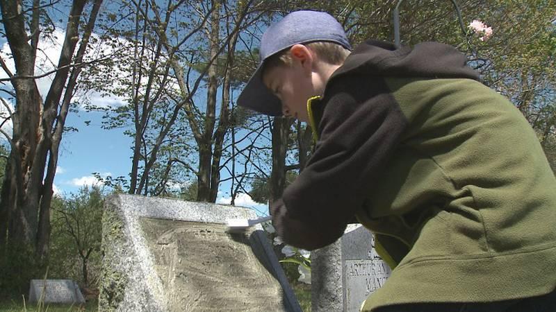 Caleb Eichsteadt cleans a headstone.