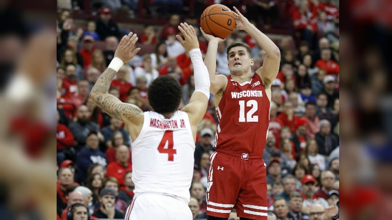 Wisconsin guard Trevor Anderson, right, goes up to shoot in front of Ohio State guard Duane...