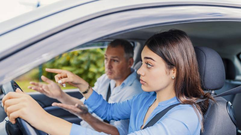 Smiling woman Learns to Drive in Car with instructor. Learning to Drive . Student driver taking...