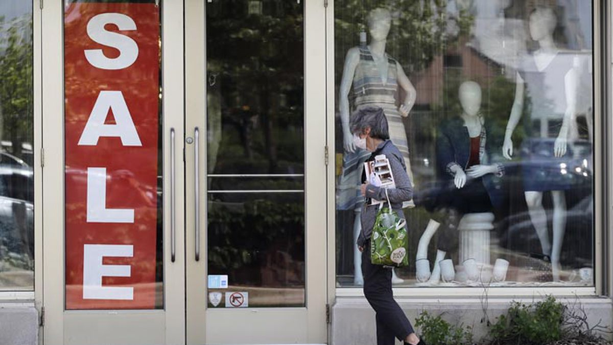 FILE - In this June 11, 2020 file photo, a woman wears a mask as she walks past a sale sign displayed at a retail store in Deerfield, Ill. The Commerce Department issues its May tally of U.S. retail sales Tuesday, June 16. (AP Photo/Nam Y. Huh, File)
